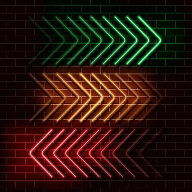 Frecce al neon verde, giallo e rosso su un muro di mattoni Vettore Premium