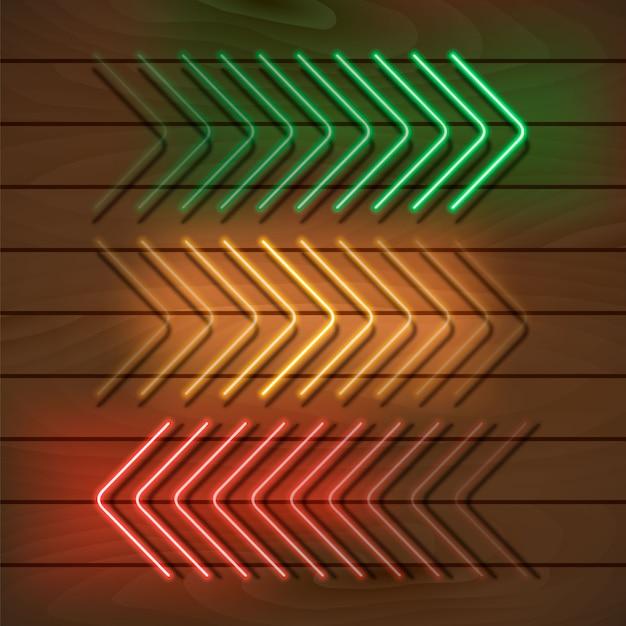 Frecce al neon verde, giallo e rosso su una parete di legno Vettore Premium