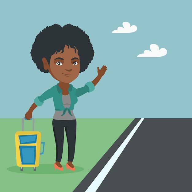 Giovane donna africana con una valigia autostop. Vettore Premium