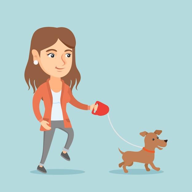 Giovane donna caucasica che cammina con il suo cane. Vettore Premium