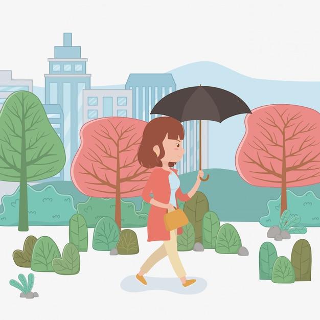 Giovane donna che cammina con l'ombrello nel parco Vettore gratuito