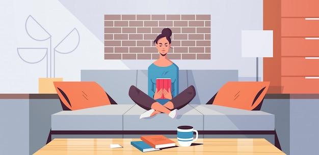 Giovane donna che si siede sullo strato facendo uso del concetto di e-learning del libro elettronico della lettura della ragazza della compressa moderno Vettore Premium