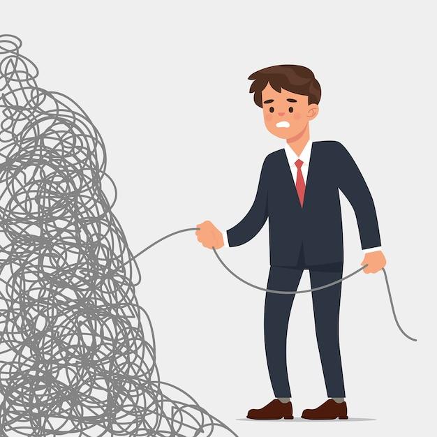 Giovane uomo d'affari tiene la fine di una corda molto aggrovigliata Vettore Premium