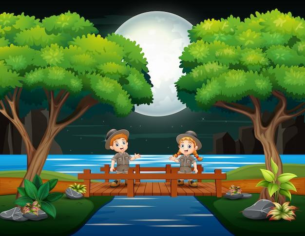 Giovani esploratori che attraversano il ponte di legno Vettore Premium