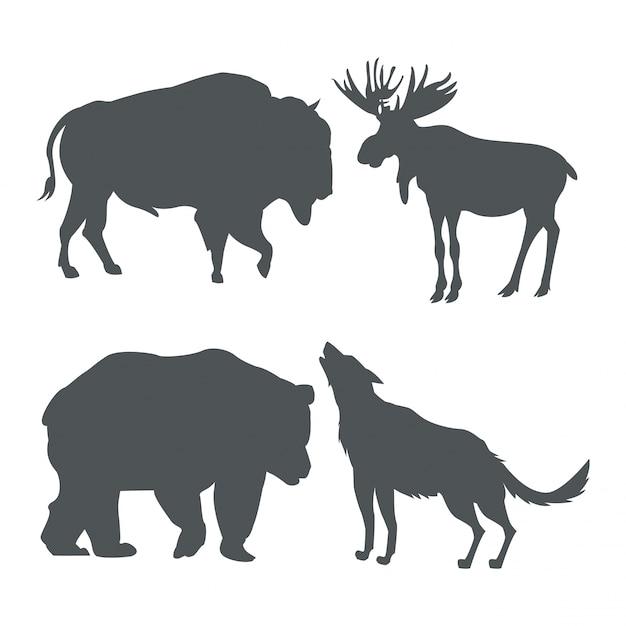 Gli animali della fauna selvatica della siluetta dell'insieme monocromatico delle montagne nevose Vettore Premium