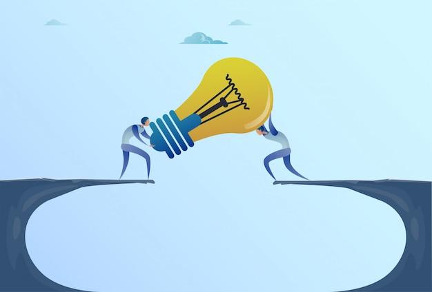 Gli uomini di affari che danno la lampadina sopra cliff gap fondano il nuovo concetto di idea di cooperazione di lavoro di squadra Vettore Premium