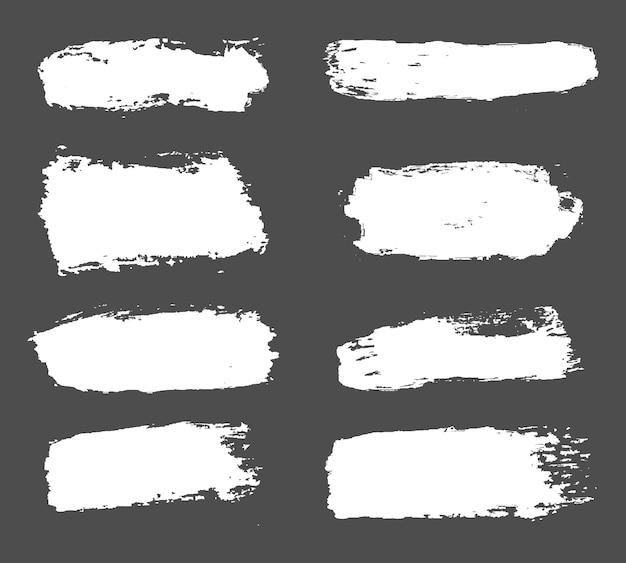 Grande collezione di vernice bianca, pennellate di inchiostro, pennelli, linee, sgangherata. Vettore Premium