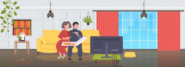 Grasso obeso uomo donna seduta sul divano a mangiare la pizza fast food malsano nutrizione concetto coppia guardare la tv sul divano moderno salotto interno a figura intera orizzontale Vettore Premium