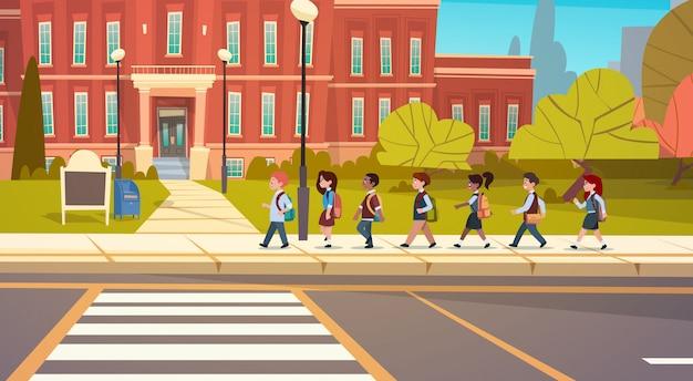 Gruppo di alunni mix race walking to school building studenti primari scolari Vettore Premium