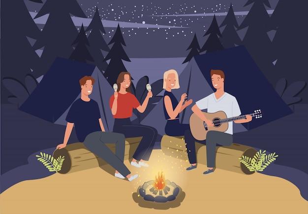 Gruppo di amici in campeggio. sono seduti attorno al fuoco del campo e suonano la chitarra Vettore Premium