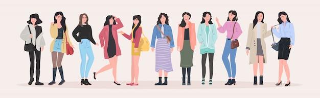 Gruppo di belle donne che stanno insieme i personaggi dei cartoni animati femminili delle ragazze attraenti in orizzontale piano integrale integrale dei vestiti di modo Vettore Premium