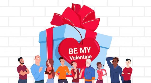 Gruppo di persone dell'insegna di giorno di biglietti di s. valentino sopra il grande contenitore di regalo con l'etichetta a forma di cuore Vettore Premium