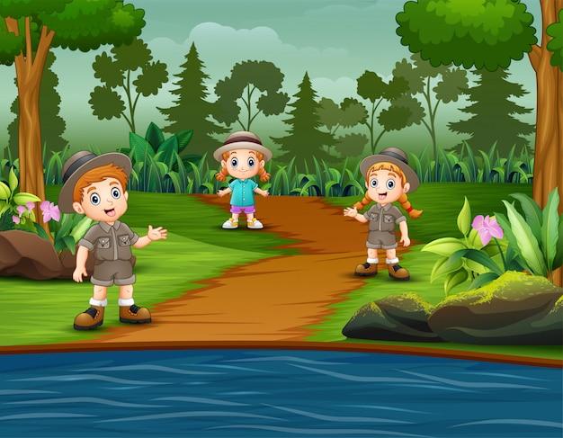 I bambini scout esplorano la foresta Vettore Premium