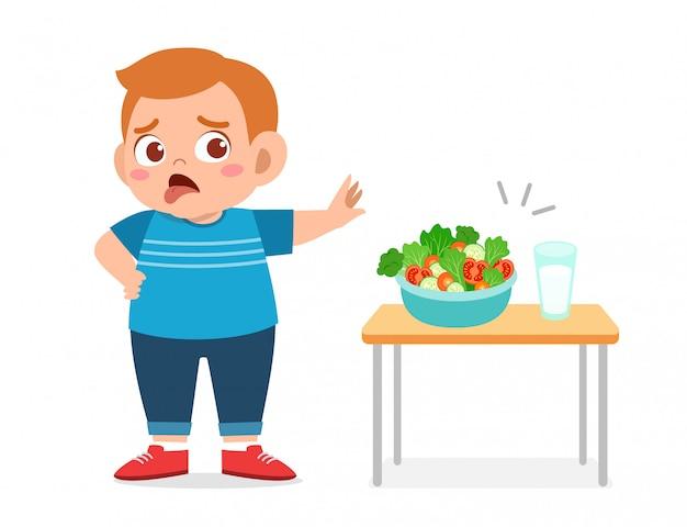 Il bambino grasso sveglio rifiuta l'alimento fresco sano Vettore Premium