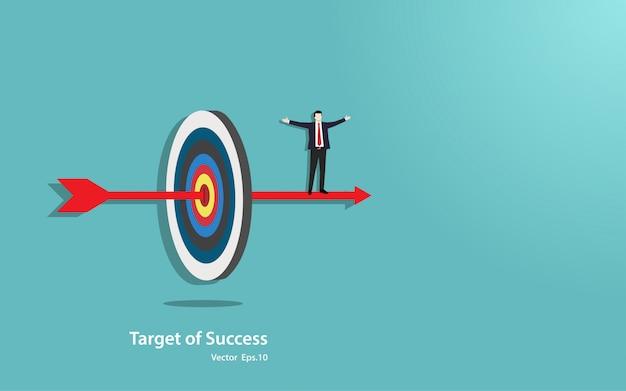 Il basamento felice dell'uomo d'affari sulla freccia penetra nel centro dell'obiettivo di successo Vettore Premium