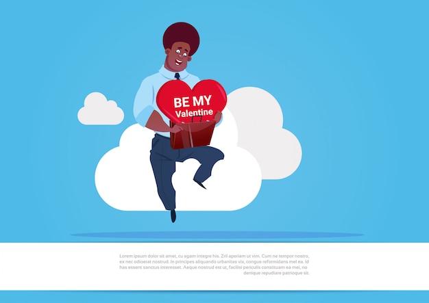 Il cuore afroamericano della tenuta dell'uomo si siede su bianco si rannuvola il fondo blu è il mio concetto di festa del giorno di amore del biglietto di s. valentino Vettore Premium