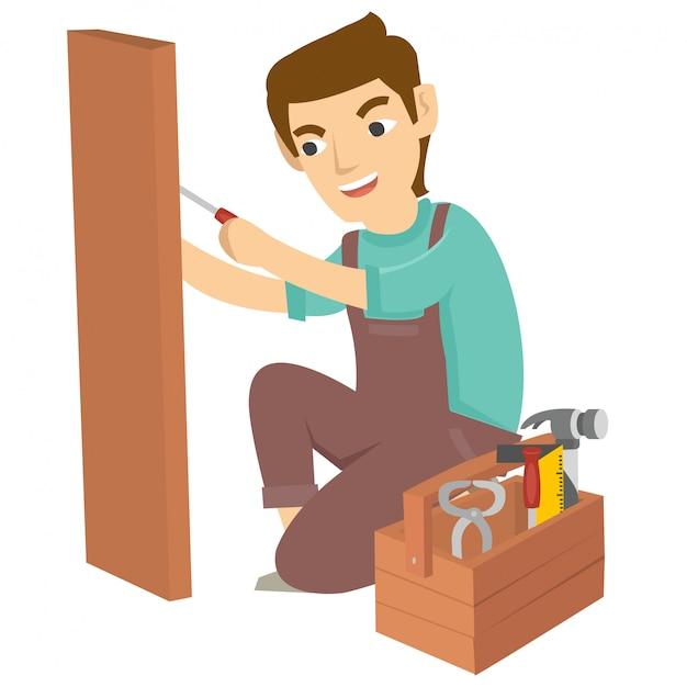 Il giovane carpentiere usa il trapano per fare un foro in legno Vettore Premium