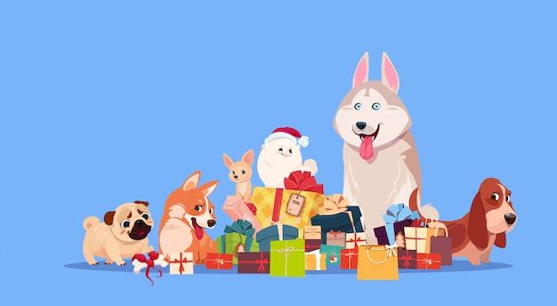 Il gruppo di cane sveglio che si siede ai regali impila synbol di decorazione del presente di festa 2018 del nuovo anno Vettore Premium