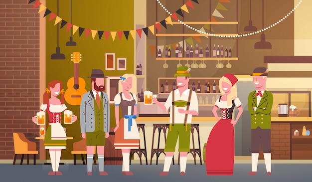 Il gruppo di persone beve la birra nell'uomo e nella donna di celebrazione del partito di oktoberfest della barra che indossano il concetto tradizionale del fest dei vestiti Vettore Premium