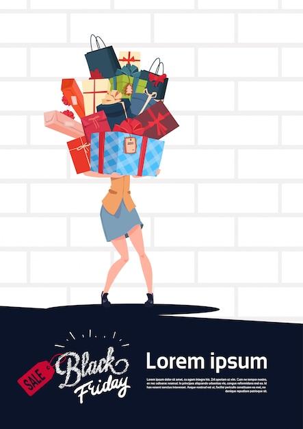 Il manifesto di vendita di black friday con i contenitori di regalo della tenuta della donna impila sopra il fondo bianco del muro di mattoni Vettore Premium