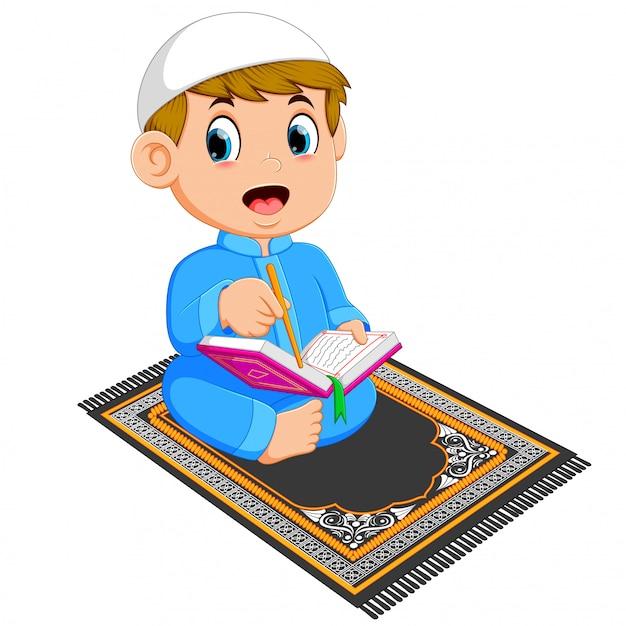 Il ragazzo con il caffetano blu sta leggendo il corano al tappeto da preghiera Vettore Premium