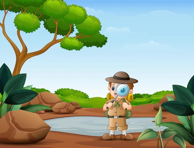 Il ragazzo esploratore con lente d'ingrandimento nella natura Vettore Premium