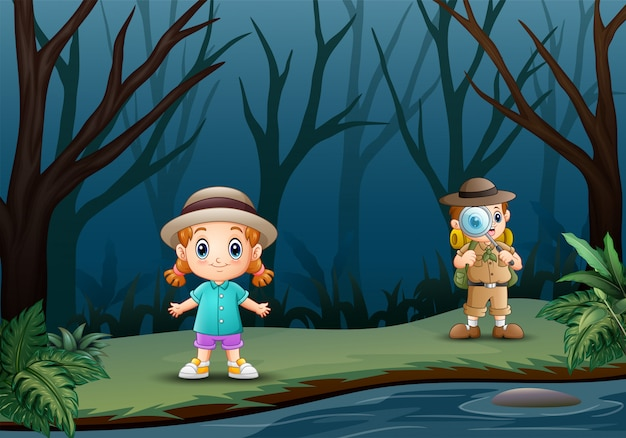 Il ragazzo esploratore con una bambina alla foresta secca Vettore Premium