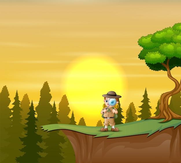 Il ragazzo esploratore sulla scogliera Vettore Premium