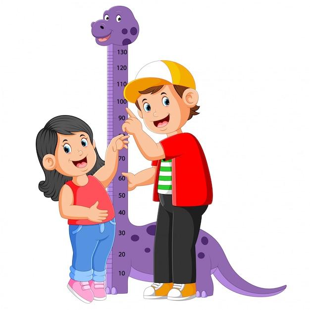 Il ragazzo sta misurando la sorella all'altezza delle misure dei dinosauri Vettore Premium