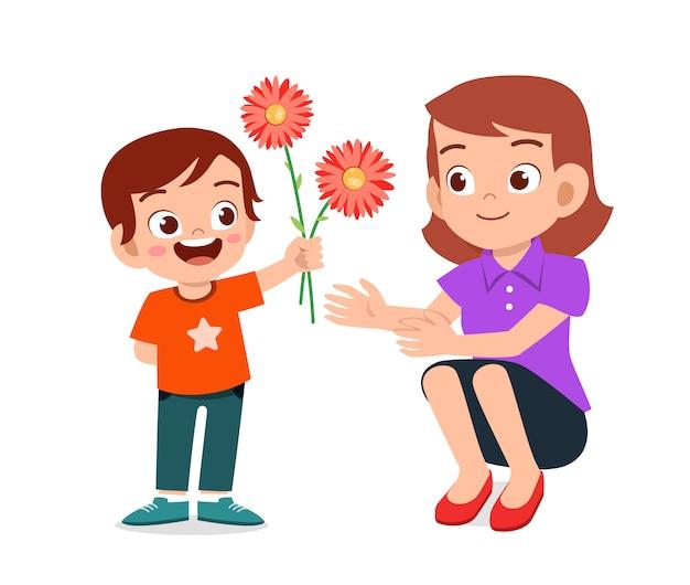 Il ragazzo sveglio felice dà il fiore alla madre Vettore Premium