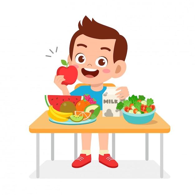 Il ragazzo sveglio felice del bambino mangia l'alimento sano Vettore Premium