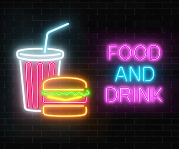 Insegna d'ardore al neon della bevanda e dell'alimento su un muro di mattoni scuro. hamburger e tazza di plastica di segni di bevande. Vettore Premium