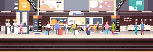 Interno della stazione ferroviaria con i passeggeri che aspettano l'insegna di orizzontale di concetto di trasporto e del trasporto di partenza Vettore Premium