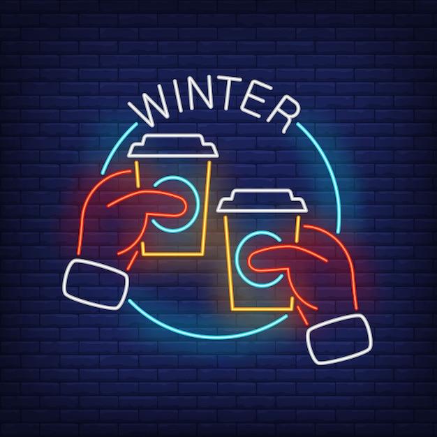 Iscrizione al neon di inverno con le mani in guanti che tengono i bicchieri di plastica Vettore gratuito