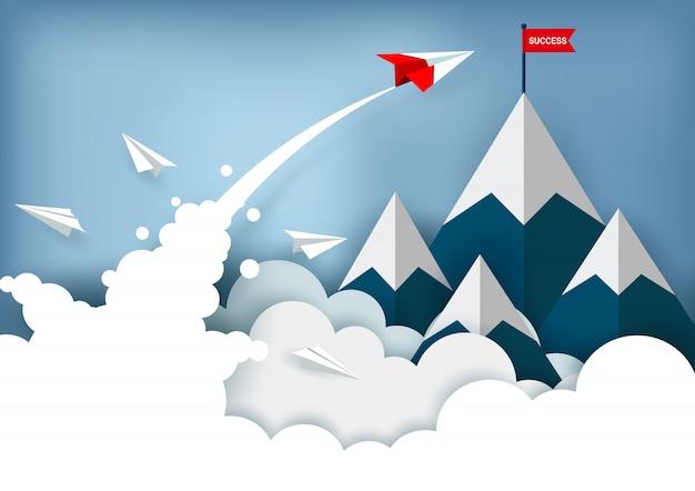 L'aereo di carta rosso sta volando verso l'obiettivo della bandiera rossa sulle montagne mentre vola sopra una nuvola Vettore Premium