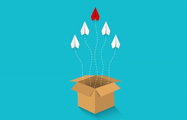 L'aereo di carta viene espulso dalla scatola marrone e va verso il cielo Vettore Premium