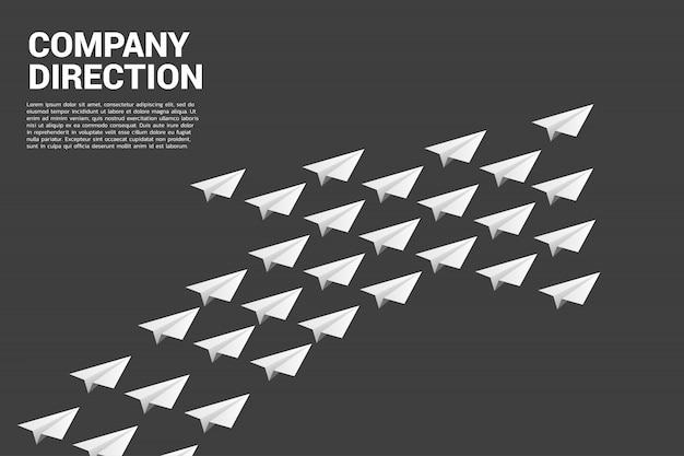 L'aeroplano di carta origami bianco è disposto a forma di grande freccia Vettore Premium