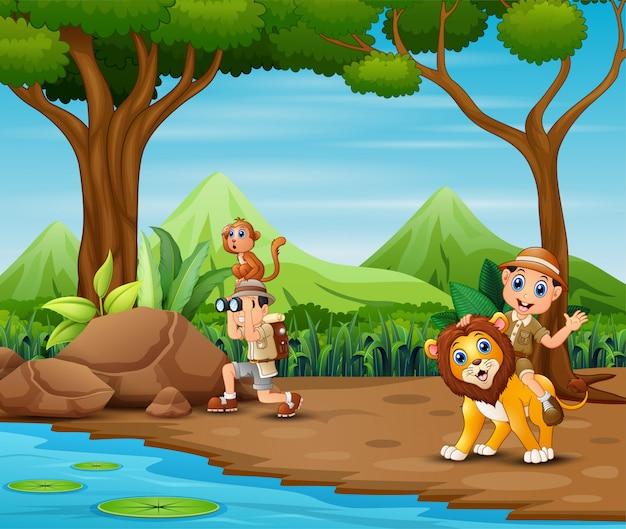 L'uomo dell'esploratore con animali nella foresta Vettore Premium