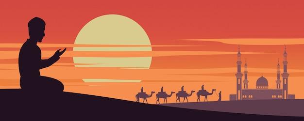 L'uomo musulmano prega mentre i musulmani della carovana guidano il cammello alla moschea Vettore Premium