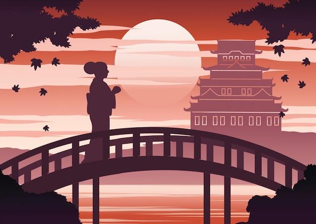La donna del giappone in vestito dal kimono si leva in piedi sul ponticello Vettore Premium