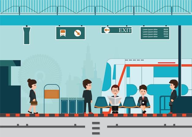 La gente aspetta un treno alla piattaforma della stazione ferroviaria. Vettore Premium