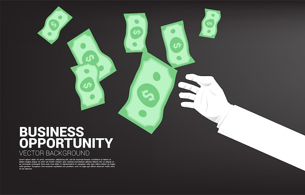 La mano dell'uomo d'affari prova a afferrare i soldi che cadono dal cielo. concetto per opportunità di business ed economia Vettore Premium