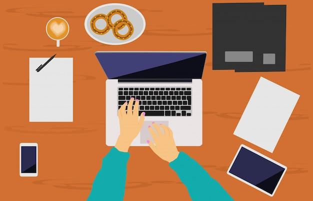 La mano di una donna sta lavorando su un quaderno posto su una scrivania di legno marrone. Vettore Premium