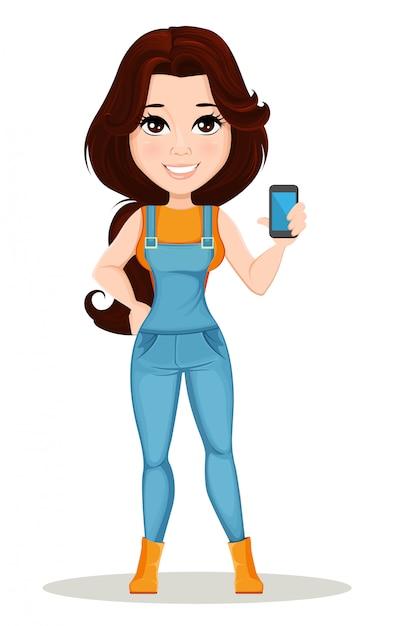 La ragazza dell'agricoltore si è vestita in tuta del lavoro tiene lo smartphone Vettore Premium