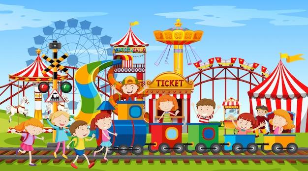La scena del parco con molte giostre e bambini felici Vettore gratuito