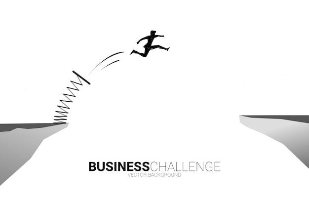 La siluetta dell'uomo d'affari salta il divario con il trampolino. concetto di spinta e crescita negli affari. Vettore Premium