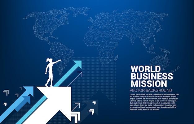 La siluetta della donna di affari indica in avanti su alzare la freccia con il fondo della mappa di mondo Vettore Premium