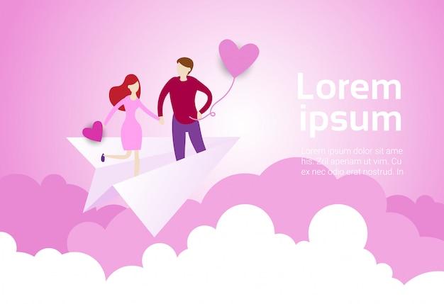 Le coppie che si tengono per mano volano sull'aereo di carta sopra il rosa Vettore Premium