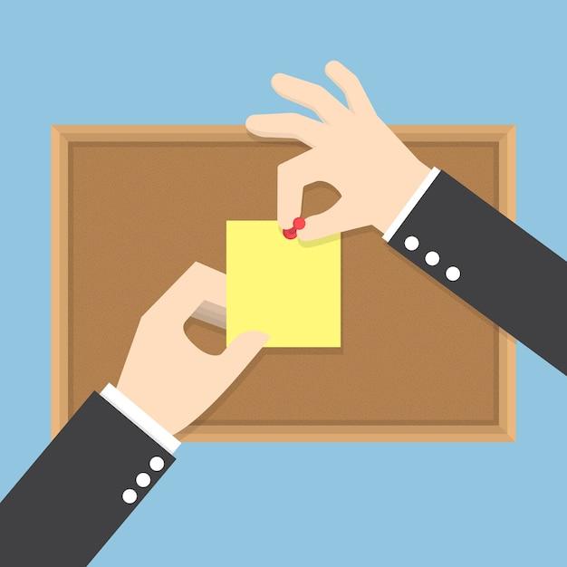 Le mani dell'uomo d'affari appuntano le note appiccicose sull'albo del sughero Vettore Premium