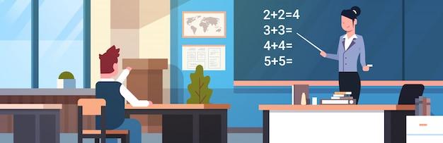 Lezione di matematica lezione insegnante femminile with pupil boy in classroom Vettore Premium